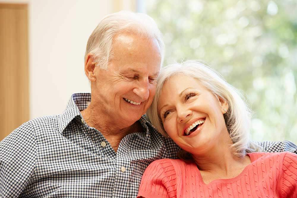 An older couple smiling and leaning into each other
